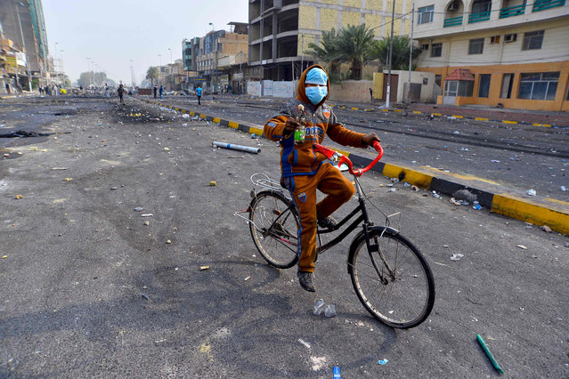 An Iraqi protester carries a petrol bomb as he rides a bike in the southern Iraqi Shiite holy city of Najaf on December 1, 2019. Protesters have hit the streets since early October in the largest grassroots movement Iraq has seen in decades, sparked by fury at poor public services, lack of jobs and widespread government graft. Security forces and armed groups responded with violence to demonstrations, killing more than 420 people and wounding 15,000, according to an AFP tally compiled from medics and an Iraqi rights commission. (Photo by Haidar Hamdani/AFP Photo)