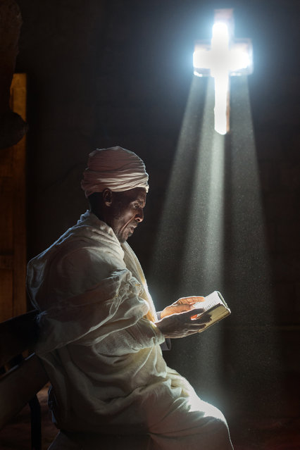 """""""Lalibela Pilgrim"""". This priest walked from his home town to attend the Christmas celebrations in Lalibela. The priest is reading a bible by the light of a cross-shaped windows in one of Lalibela's famous rock-hewn churches. Photo location: Lalibela, Ethiopia. (Photo and caption by Sean Caffrey/National Geographic Photo Contest)"""
