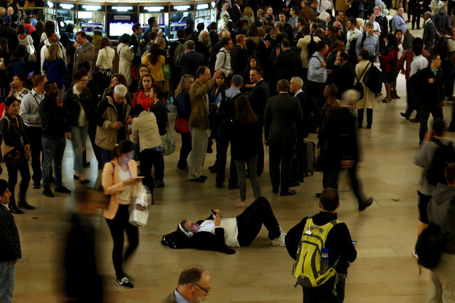 A man rests on the floor as stranded commuters fill Grand Central Terminal, after commuter rail service in and out of the terminal was suspended during the evening rush hour on Tuesday due to a fire under a section of elevated tracks, in New York, United States, May 17, 2016. (Photo by Eduardo Munoz/Reuters)