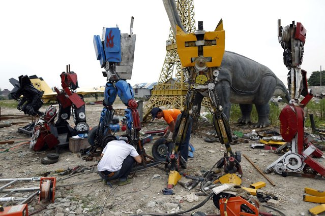 """Workers work on """"Transformers"""" replicas on the outskirts of Shanghai, June 18, 2014. Li Lei, owner of a small factory, uses his spare time and money to build """"Transformers"""" replicas for rent or sale. The new Transformers movie, which is premiering later this month, has brought the factory many new orders, according to Li. (Photo by Aly Song/Reuters)"""