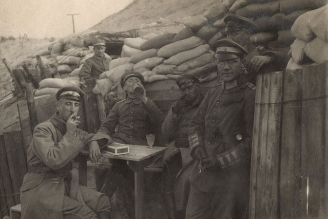 German officers sit outside dugouts on the Yser Front in Belgium in this 1917 handout picture. This picture is part of a previously unpublished set of World War One (WWI) images from a private collection. The pictures offer an unusual view of varied and contrasting aspects of the conflict, from high tech artillery to mobile pigeon lofts, and from officers partying in their headquarters to the grim reality of life and death in the trenches. The year 2014 marks the centenary of the start of the war. (Photo by Reuters/Archive of Modern Conflict London)