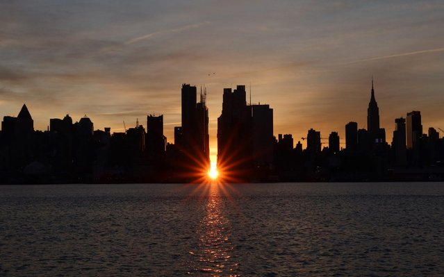 The sun rises during a Manhattanhenge sunrise along 42nd Street behind the skyline of midtown Manhattan and the Empire State Building in New York City on November 30, 2019 as seen from Weehawken, New Jersey. (Photo by Gary Hershorn/Getty Images)