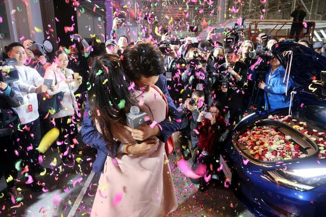 A Tesla employee proposes to his girlfriend with a China-made Tesla Model 3 vehicle filled with flowers at a delivery ceremony in the Shanghai Gigafactory of the U.S. electric car maker in Shanghai, China on December 30, 2019. (Photo by Yilei Sun/Reuters)