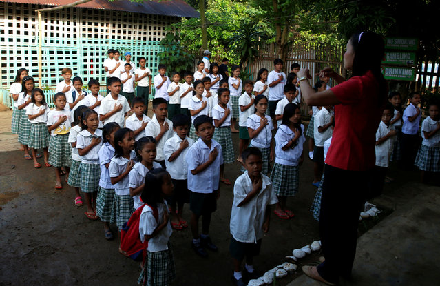 A teacher leads the singing of the Philippine National anthem , during the opening of classes at a remote Casili Elementary School in Montalban, Rizal northeast of Manila, Philippines June 13, 2016. (Photo by Erik De Castro/Reuters)