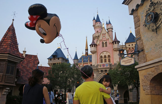 In this September 11, 2015 photo, a girl holds a balloon featuring Minnie Mouse at the Hong Kong Disneyland. Hong Kong Disneyland opened in 2005 and has been faulted for a lack of big ticket attractions and its small size, at less than 121 hectares (300 acres). One time, the park shut its gates because it was full, turning away hundreds of mainland Chinese and Taiwanese ticket holders, some of whom tried to force their way in. (Photo by Kin Cheung/AP Photo)