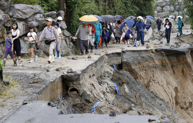 In this July 6, 2017 photo,  local residents walk on a damaged road to a safer place following the flooding caused by heavy rain in Asakura, Fukuoka prefecture, southwestern Japan. Troops worked Thursday to rescue hundreds of people stranded by flooding in southern Japan. (Photo by Takuto Kaneko/Kyodo News via AP Photo)