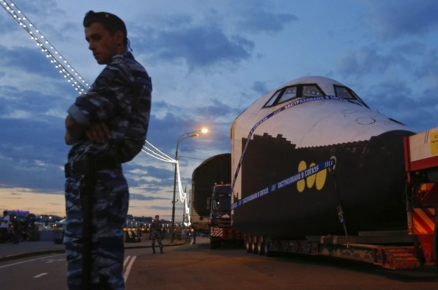 A police officer stands guard in front of a life-sized model of Soviet-made Buran space orbiter, which was moved from Maxim Gorky Central Park for Culture and Recreation to the All-Russia Exhibition Centre (VDNKh) through the streets of Moscow June 5, 2014. While this model was used for tests during the Buran Programme, the actual Buran, the former flagship of the Soviet space fleet, will be placed as a showpiece on one of the squares of VDNKh in Moscow. (Photo by Maxim Shemetov/Reuters)