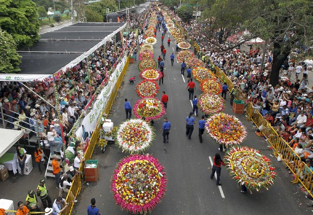 """Flower growers known as """"silleteros"""" carry their flower arrangements during the annual flower parade in Medellin, Colombia, August 9, 2015. (Photo by Fredy Builes/Reuters)"""