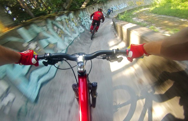 Downhill bikers Kemal Mulic (C) and Kamer Kolar train on the disused bobsled track from the 1984 Sarajevo Winter Olympics on Trebevic mountain near Sarajevo, Bosnia and Herzegovina, in this picture taken remotely with a camera mounted on the helmet of Tarik Hadzic August 8, 2015. Abandoned and left to crumble into oblivion, most of the 1984 Winter Olympic venues in Bosnia's capital Sarajevo have been reduced to rubble by neglect as much as the 1990s conflict that tore apart the former Yugoslavia. (Photo by Dado Ruvic/Reuters)
