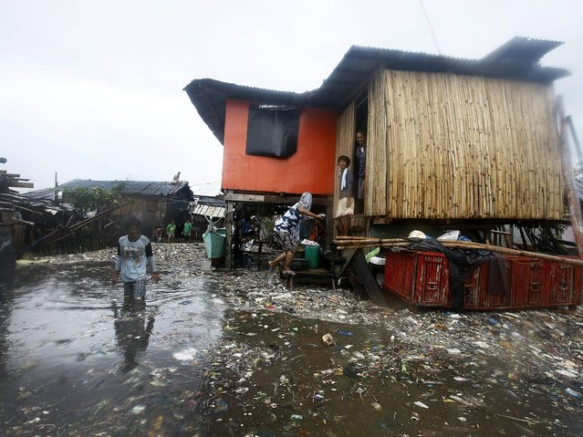 Filipino residents view their flooded surrounding caused by strong winds and rain brought by typhoon Rammasun along the coastline of the Tondo slum area, in Manila, Philippines, 16 July 2014. (Photo by Dennis M. Sabangan/EPA)
