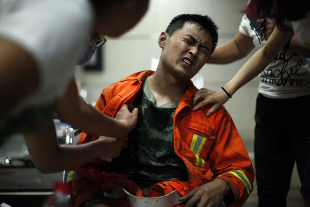 An injured firefighter grimaces as he is examined in a hospital following explosions in northeastern China's Tianjin municipality, Thursday, August 13, 2015. (Photo by Chinatopix Via AP Photo)