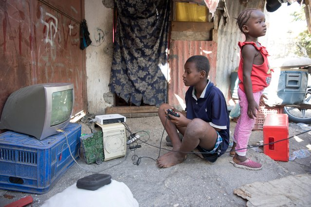 A boy plays video games on the street, outside of Notre Dame de l'Assomption Cathedral (Our Lady of the Assumption), in Port-au-Prince, January 10, 2020. Estimates of the number of dead vary widely, from below 100,000 to as high as the government's 316,000. There is also no consensus over how much aid Haiti actually received - or what constitutes aid - but most experts put it at more than $10 billion. (Photo by Valerie Baeriswyl/Reuters)