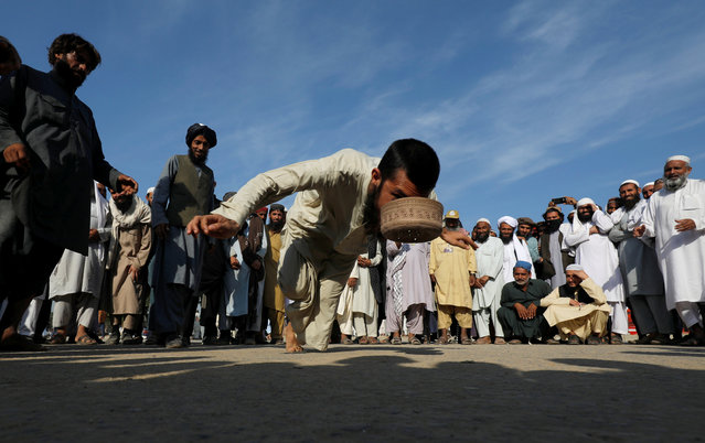 """A supporter of the religious and political party Jamiat-Ulema-e-Islam (JUI-F) plays """"topai"""" (cap), a traditional game that consists on  picking a cap with the mouth while balancing on a toe, during the so called Azadi March (Freedom March), called by the opposition, to protest against the government of Prime Minister Imran Khan in Islamabad, Pakistan on November 5, 2019. (Photo by Akhtar Soomro/Reuters)"""