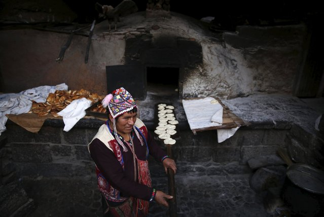 Baker Eulogio Pillco bakes traditional bread using an oven made of clay in the town of Pisac, Cusco, August 13, 2015. Pillco, who wears traditional Andean clothes, has been baking for 30 years, following in the footsteps of his father who taught him the craft. (Photo by Pilar Olivares/Reuters)