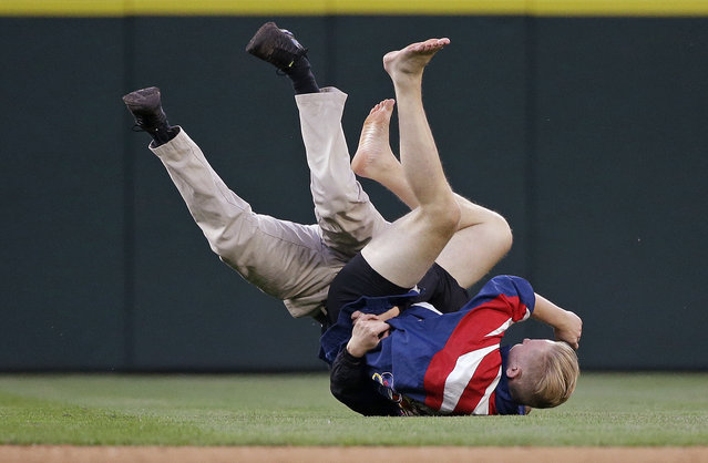 A ballpark security worker, left, tackles and upends a fan who ran onto the outfield during play in the fifth inning of a baseball game between the Seattle Mariners and St. Louis Cardinals on Saturday, June 25, 2016, in Seattle. (Photo by Elaine Thompson/AP Photo)