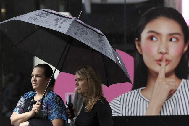 Women shelter under an umbrella as rain falls in Sydney, Friday, February 7, 2020, while the Bureau of Meteorology issued severe weather warning along the New South Wales state coast. The rain comes as a slight relief for some areas dealing with wildfires that devastated large swathes of land across the state over the last several months. (Photo by Rick Rycroft/AP Photo)