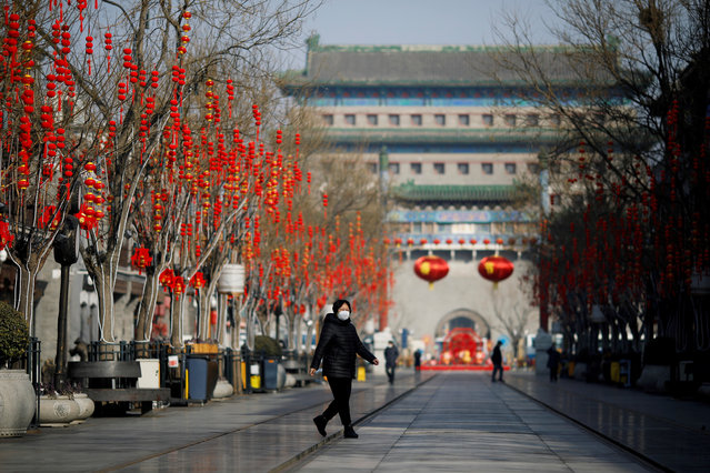 A woman wearing a face mask walks on the Qianmen pedestrian street in the morning after the extended Lunar New Year holiday caused by the novel coronavirus outbreak, in Beijing, China on February 10, 2020. (Photo by Carlos Garcia Rawlins/Reuters)