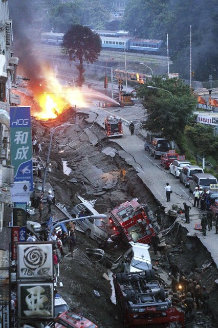 Vehicles are left lie in a destroyed street as part of the street is burning with flame following multiple explosions from an underground gas leak in Kaohsiung, Taiwan, early Friday, August 1, 2014. (Photo by AP Photo)
