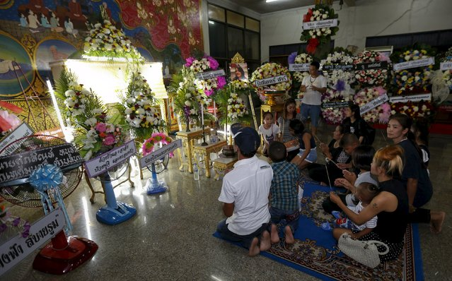 Relatives of Waraporn Changtam, a Thai victim of Monday's bomb blast, prays during a Buddhist funeral at a temple in Nonthaburi province, on the outskirts of Bangkok, Thailand, August 19, 2015. (Photo by Chaiwat Subprasom/Reuters)