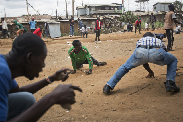 Supporters of opposition leader Raila Odinga duck for cover as they come under fire from Kenyan security forces in the Kibera slum of Nairobi, Kenya, Saturday August 12, 2017. Violent demonstrations have erupted in some areas after President Uhuru Kenyatta was declared victorious of the presidential election. (Photo by Jerome Delay/AP Photo)