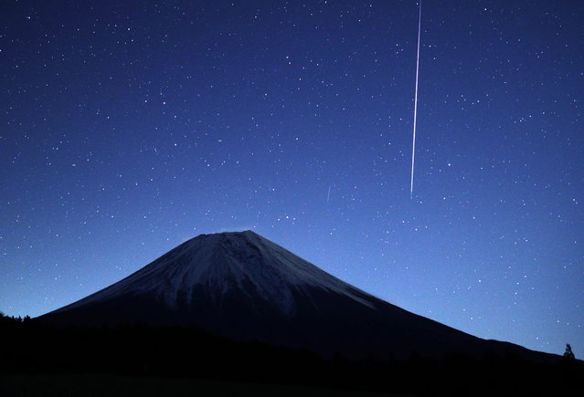 A meteor from the Geminids meteor shower streaks across the sky above Mount Fuji in Fujinomiya, Shizuoka prefecture, Japan, 14 December 2018. (Photo by EPA/EFE/JIJI Press)