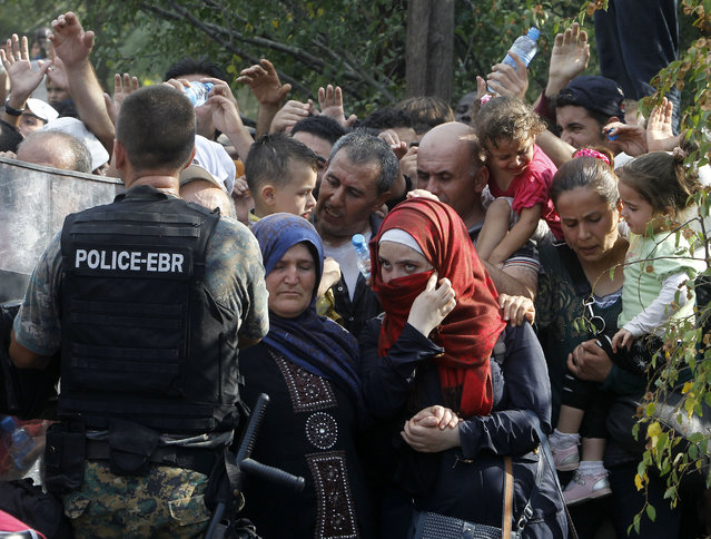Migrants wait to enter Macedonia from Greece on the border line with Greece, near the southern Macedonia's town of Gevgelija, Friday, August 21, 2015. About 39,000 people, mostly Syrian migrants, have been registered as passing through Macedonia in the past month, twice as many as the month before. (Photo by Boris Grdanoski/AP Photo)