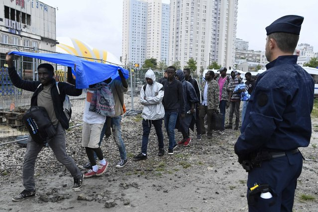 French anti-riot police force CRS officers stand by as migrants arrive to board buses during the evacuation of a makeshift camp at Porte de la Chapelle, in the north of Paris, on August 18, 2017. More than a thousand migrants and refugees were evacuated on early August 18 from a makeshift camp that had been set up for several weeks in La Chapelle. (Photo by Bertrand Guay/AFP Photo)