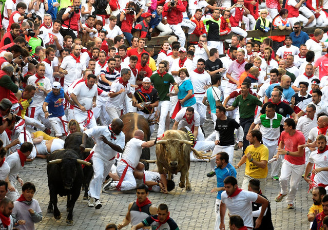 Runners fall in front of Fuente Ymbro fighting bulls near the entrance to the bullring, during the first running of the bulls at the San Fermin festival in Pamplona, northern Spain, July 7, 2016. (Photo by Eloy Alonso/Reuters)