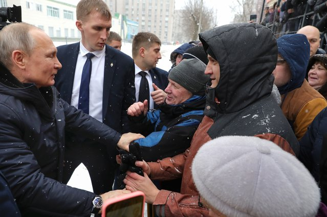 Russian President Vladimir Putin, left, greets local people as he visits an industrial college in Cherepovets, Russia, Tuesday, February 4, 2020. Putin said that a nationwide vote on constitutional changes he proposed wouldn't be used to extend his current term in office but remained coy about his future political plans. (Photo by Mikhail Klimentyev/Sputnik/Kremlin Pool Photo via AP Photo)