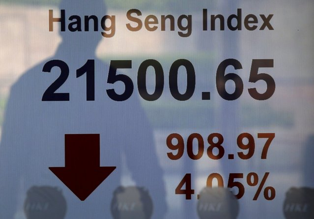 A passerby is reflected on a panel displaying the Hang Seng Index, which drops more than four percent, at the Hong Kong Stocks Exchange in Hong Kong, China August 24, 2015. (Photo by Bobby Yip/Reuters)