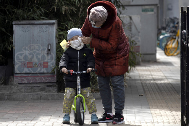 A woman wipes the face of a child on the streets of Beijing on Thursday, March 12, 2020. For most people, the new coronavirus causes only mild or moderate symptoms. For some it can cause more severe illness, especially in older adults and people with existing health problems. (Photo by Ng Han Guan/AP Photo)