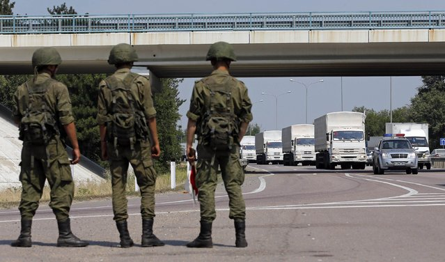 A Russian convoy of trucks carrying humanitarian aid for Ukraine drives along a road as Russian servicemen look on, near Kamensk-Shakhtinsky, Rostov Region, August 14, 2014. (Photo by Maxim Shemetov/Reuters)