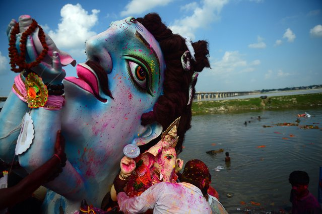 Indian Hindu devotees carry an idol of the elephant-headed Hindu deity Ganesha for immersion in a temporary pond near Sangam in Allahabad on September 4, 2017. The Ganesh Chaturthi festival is a popular 11-day religious festival which is annually celebrated across India. (Photo by Sanjay Kanojia/AFP Photo)