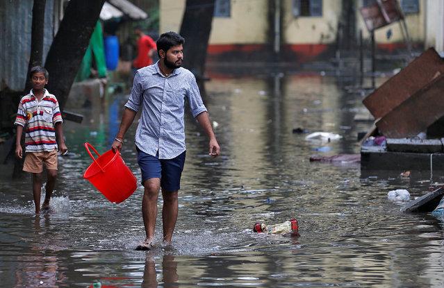 A man carrying a bucket walks through a water-logged neighbourhood in Mumbai, August 30, 2017. (Photo by Danish Siddiqui/Reuters)