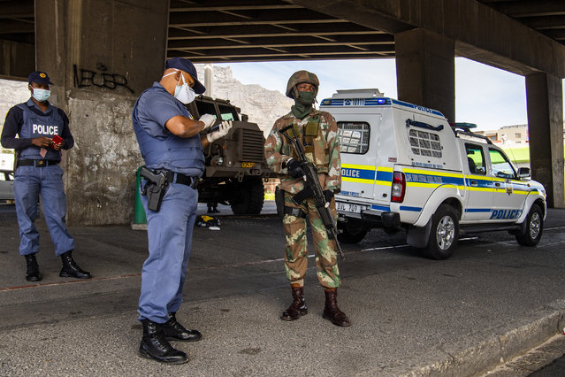 A policeman and soldier man a roadblock in Cape Town, South Africa, Friday, March 27, 2020, after South Africa went into a nationwide lockdown for 21 days in an effort to mitigate the spread to the coronavirus. (Photo by AP Photo/Stringer)
