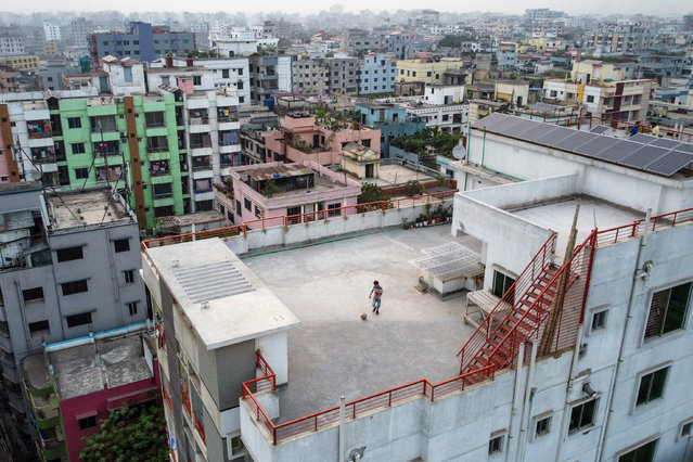 This picture taken on March 23, 2020 shows Samin Sharar, 9, playing on the rooftop of his building in Dhaka, as he avoids going out due to fears over the COVID-19 novel coronavirus. Over a 24-hour period, in a world where a third of humanity is now under orders to stay home, AFP photographers have captured snapshots of daily life during the coronavirus pandemic. (Photo by Munir Uz Zaman/AFP Photo)
