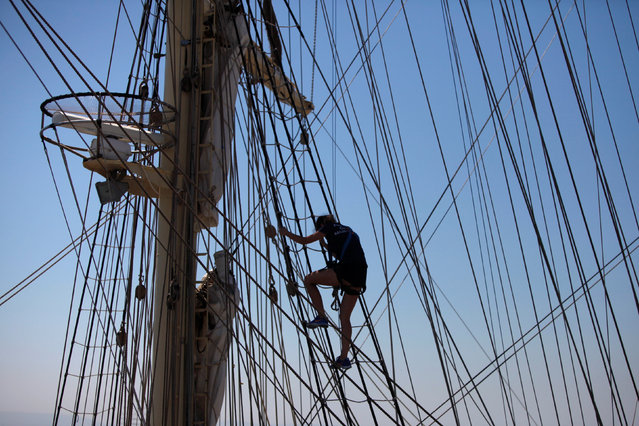 "Crew members prepare a ship before the beginning of the Tall Ships Races 2016 parade, in Lisbon, Portugal, July 25, 2016. The Tall Ships' Races are races for sail training ""tall ships"" (sailing ships). The races are designed to encourage international friendship and training for young people in the art of sailing. The races are held annually in European waters and consists of two racing legs of several hundred nautical miles, and a ""cruise in company"" between the legs. Over one half (fifty-percent) of the crew of each ship participating in the races must consist of young people. (Photo by Pedro Nunes/Reuters)"