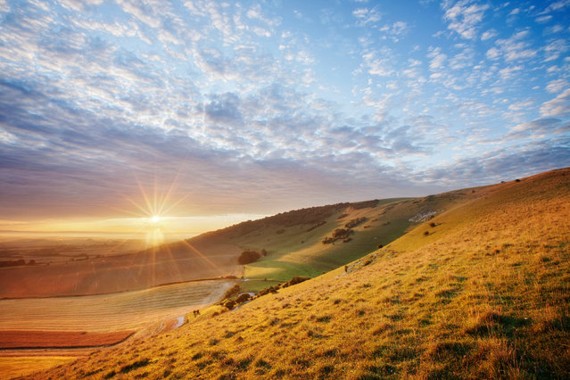 Sunrise over chalk downland viewed from Wilmington Hill in South Downs National Park, England on March 30, 2020. The South Downs National Park is celebrating its 10th anniversary by renewing its commitment to protecting the biodiversity of the beauty spot as the challenges caused by climate change intensify. (Photo by Guy Edwardes/National Trust/PA Wire Press Association)