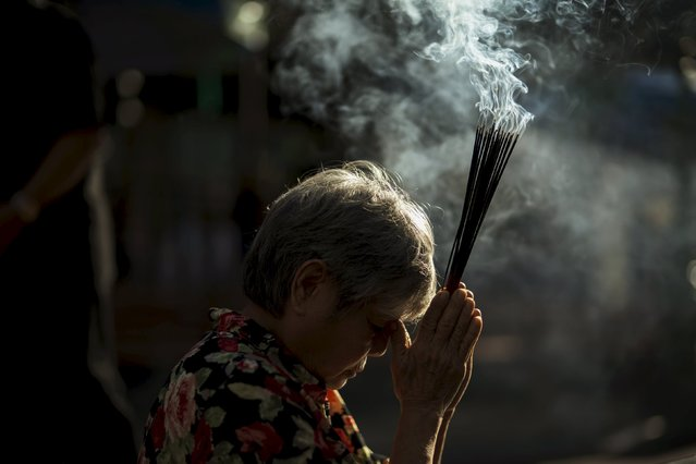 A woman holds up joss sticks as she prays after a religious ceremony at the Erawan shrine, the site of a recent deadly blast, after its was repaired, in central Bangkok, Thailand, September 4, 2015. (Photo by Athit Perawongmetha/Reuters)