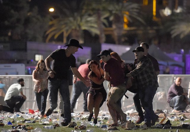 People carry a peson at the Route 91 Harvest country music festival after apparent gun fire was heard on October 1, 2017 in Las Vegas, Nevada. There are reports of an active shooter around the Mandalay Bay Resort and Casino. (Photo by David Becker/Getty Images)