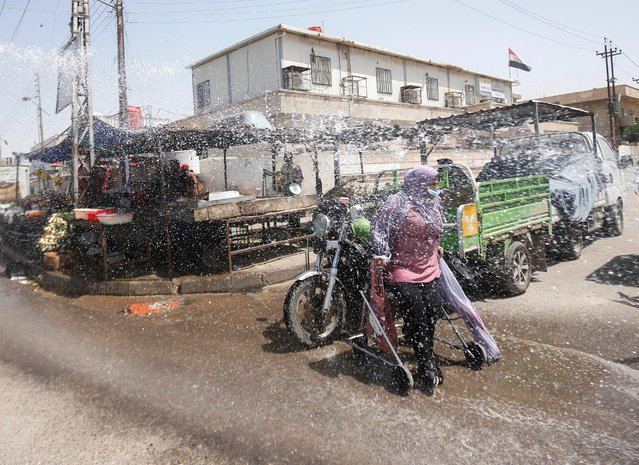 A woman wearing a protective face mask stands on her walker, as riot police spray sterile water in the streets and markets, following the outbreak of coronavirus disease (COVID-19), as they used to spray water on demonstrators, in Basra, Iraq on March 31, 2020. (Photo by Essam al-Sudani/Reuters)
