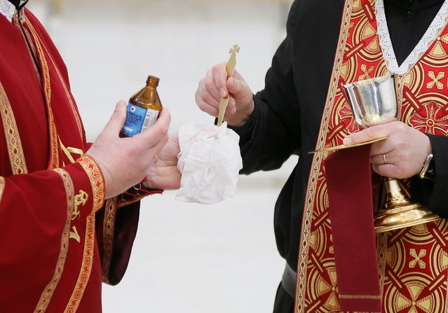Clergymen disinfect the holy spoon for communion, as a measure to prevent the spread of coronavirus disease (COVID-19), during a service at the Cathedral of the Resurrection of Christ in Kiev, Ukraine on March 22, 2020. (Photo by Valentyn Ogirenko/Reuters)
