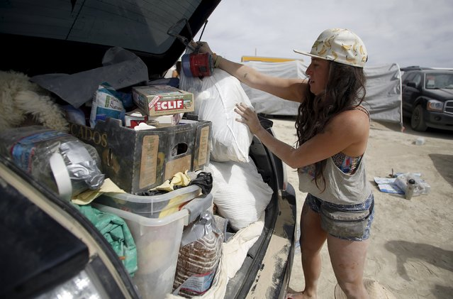 """Anna Kallett packs her car before departing during the Burning Man 2015 """"Carnival of Mirrors"""" arts and music festival in the Black Rock Desert of Nevada September 5, 2015. (Photo by Jim Urquhart/Reuters)"""