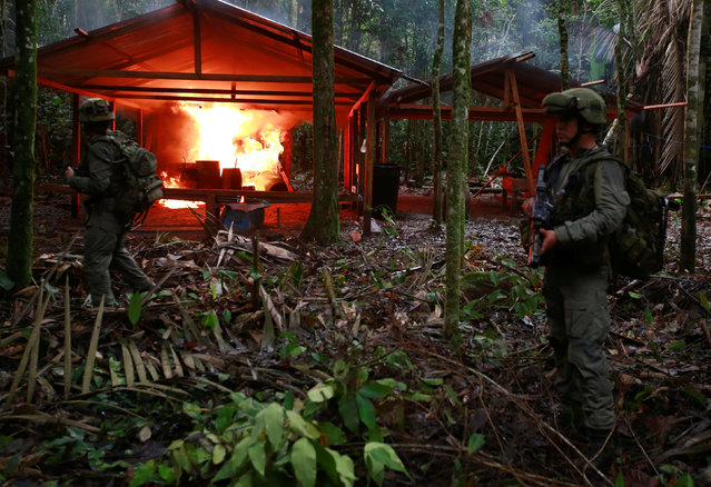 A Colombian anti-narcotics policeman stands guard after burning a cocaine lab, which police said belongs to criminal gangs, in a rural area of Calamar in Guaviare state, Colombia, August 2, 2016. (Photo by John Vizcaino/Reuters)