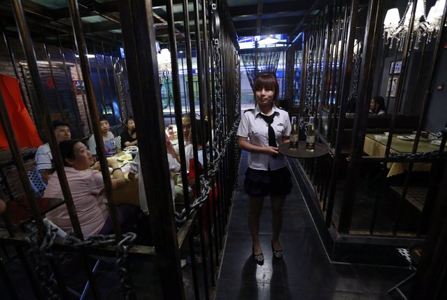 A waitress poses while customers eat dinner inside iron cages at a jail-themed restaurant in the Chinese port city of Tianjin September 9, 2014. The three-story restaurant consists of rooms resembling jail's cells made from iron caging and it attracts customers who wants to experience the atmosphere of the jail for fun. (Photo by Kim Kyung-Hoon/Reuters)