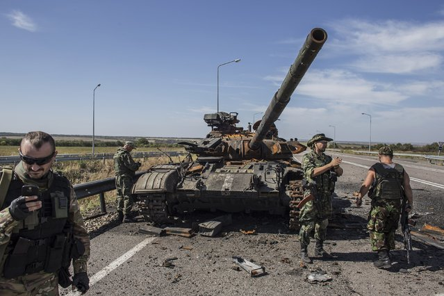Pro-Russian rebels stand near a burnt-out Ukrainian tank outside the destroyed airport in Luhanks, eastern Ukraine, September 14, 2014. (Photo by Marko Djurica/Reuters)