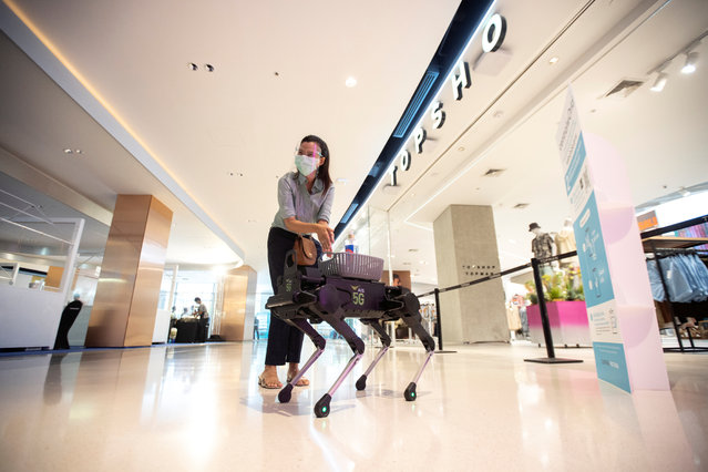"A woman uses a sanitising hand gel from a four-legged dog robot called ""K9"" at the Central World department store, after the Thai government eased isolation measures to prevent the spread of the coronavirus disease (COVID-19) in Bangkok, Thailand, May 17, 2020. (Photo by Athit Perawongmetha/Reuters)"