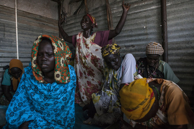 Women pray at a Pentecostal church in the Protection of Civilians (POC) site at the United Nations Mission in South Sudan (UNMISS) compound in Malakal, South Sudan on Saturday, July 9, 2016. (Photo by Jane Hahn/The Washington Post)