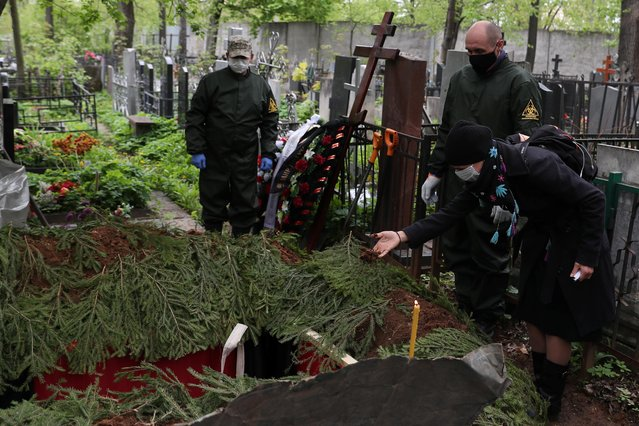 A mourner wearing a protective face mask throws ground into the grave of Orthodox deacon Andrei Molchanov, 54, who died after contracting the coronavirus disease (COVID-19), during a funeral at a cemetery in Moscow, Russia on May 9, 2020. (Photo by Evgenia Novozhenina/Reuters)