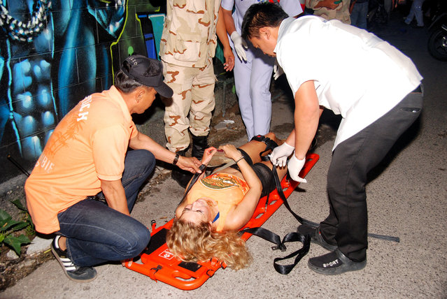 In this Thursday, August 11, 2016, photo, rescue workers help an unidentified woman after a bomb blast in the southern resort city of Hua Hin, 240 kilometers (150 miles) south of Bangkok, Thailand. (Photo by Daily News via AP Photo)